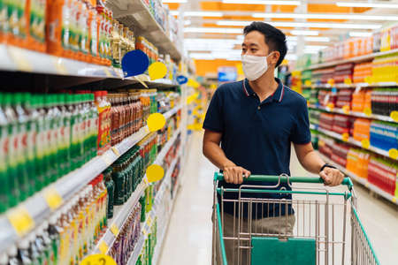 Young adult Asian man wearing a face mask while shopping with cart trolley in grocery supermarket store. Hes choosing to buy products in the grocery store during Covid 19 crisis in Thailand Stock Photo
