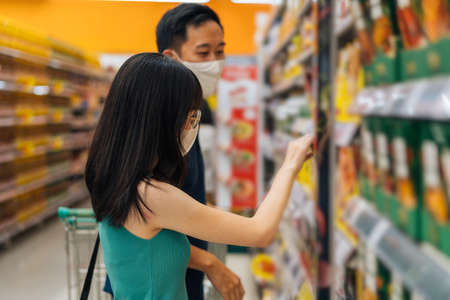 Woman and man shopping in grocery store wearing protective face coverings, choosing food in supermarket aisle, looking at products, grocery shopping during the pandemic Imagens