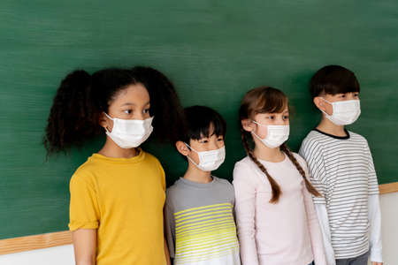 Group of diverse elementary students in classroom. Primary school multi-racial pupils standing in a row wearing a face mask with blackboard in background. School new normal concept