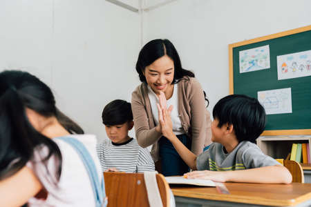 Young Asian teacher giving boy high five in school, success, achievement, happiness. Asia school boy with young woman in class. 版權商用圖片