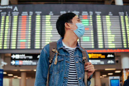 Asian male traveler wearing a face mask waiting for boarding airplane. Young tourist waiting in airport with departure board in background during Covid-19 virus pandemic