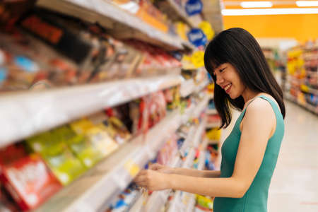 Side view of Asian woman shopping in grocery store and smiling, buying food, standing in supermarket aisle looking at products, grocery shopping Reklamní fotografie
