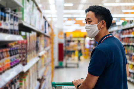 Young adult Asian man wearing a face mask while shopping with cart trolley in grocery supermarket store. Hes choosing to buy products in the grocery store during Covid 19 crisis in Thailand