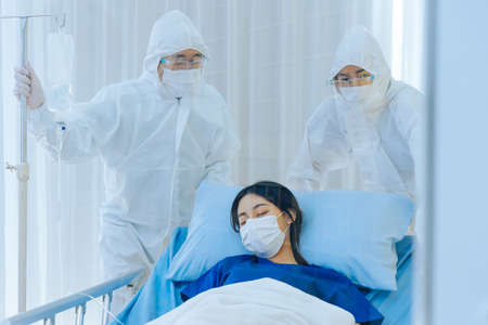 Young Asian woman infected by wearing mask under oxygen saturation treatment being taken by doctors for observation for urgent responding and emergency due to respiratory failure