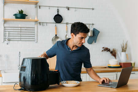 Handsome young caucasian man looking at instructions online on laptop on how to use modern air fryer to cook healthy food without using oil at home in kitchen
