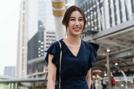 Confident and independent young Asian woman in casual clothing smiling and walking down the city street in during daytime