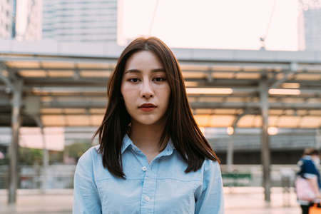 Portrait of thoughtful young Asian businesswoman standing looking at camera feeling depressed and unhappy standing in city street