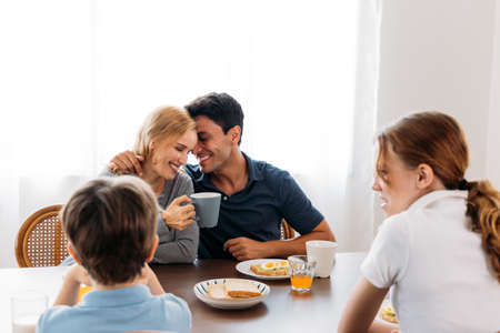 Romantic family of young man and woman embracing while holding cup of coffee and enjoying morning healthy breakfast with son and daughter at home