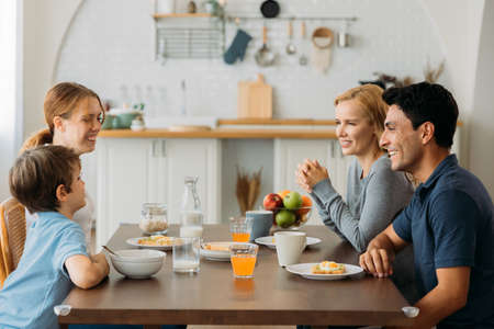 Smiling caucasian family of man and woman sitting together and listening to small and cute son with daughter while eating healthy breakfast at home Banque d'images