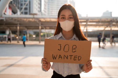 Young upset Asian woman wearing covid-19 protective face mask asking for job via message on signboard after losing job due to coronavirus pandemic and outbreak Banque d'images