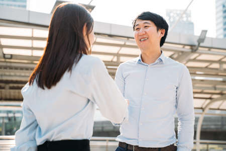Portrait of smiling young handsome Asian businessman shaking hands with a young woman employee outside office after being selected for job