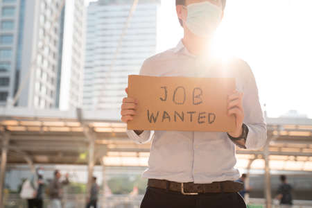 Depressed man wearing covid-19 surgical face mask asking for job via message on cardboard placard after losing job due to coronavirus pandemic