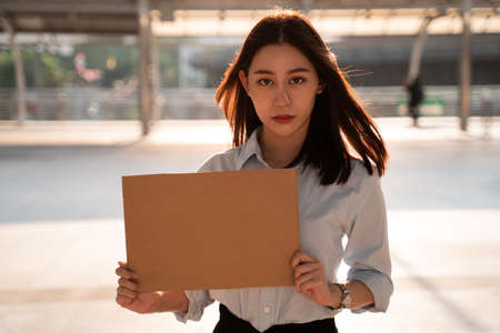 Portrait of depressed young Asian woman in formal clothing seeking for job after being fired from office holding a black cardboard placard on city street