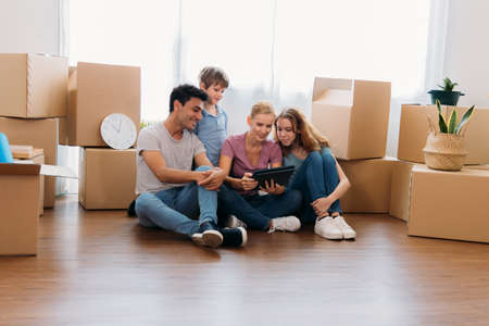 Cheerful and beautiful caucasian mother holding digital tablet and shopping for furniture for new home with handsome husband and children with cardboard boxes around