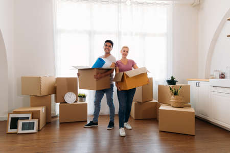 Portrait of happy young caucasian husband and wife posing in their new house and holding cardboard boxes while moving in and looking at camera