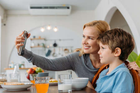 Beautiful young caucasian mother smiling and taking selfie photo using smartphone with cute little son at dining table during breakfast Banque d'images
