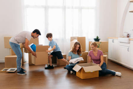 Beautiful young mother sitting on wooden floor with daughter packing stuff in cardboard boxes with handsome father and son moving boxes during shift to new house