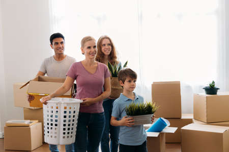 Young caucasian mother with husband and children unpacking things from cardboard boxes in new home and setting them in proper place