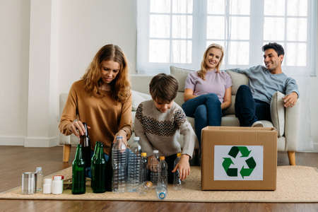 Teenage caucasian sister with younger brother organizing plastic and glass bottles for recycle while mother and father sitting on couch watching them at home Banque d'images