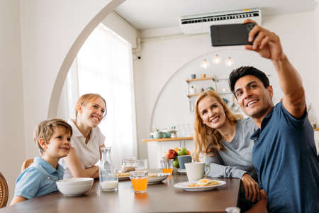 Caucasian Family group of four taking selfie photo while eating a breakfast on dining table. Father, Mother, Daughter and Son enjoying happy time together with kitchen in background.