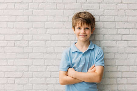 Portrait of happy young caucasian boy in casual outfit with arms crossed isolated over white bricks background smiling and looking at camera