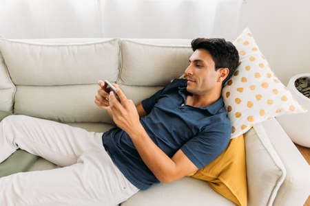 Handsome young caucasian man lying on sofa in a comfortable position playing games and watching video on smartphone during free time at home