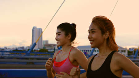 Two healthy and fit young female friends jogging on city street during early morning while talking and smiling in city