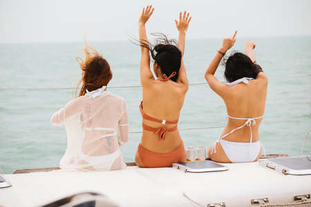 Side view of young long-haired women in colorful bikini dancing on yacht in calm sea