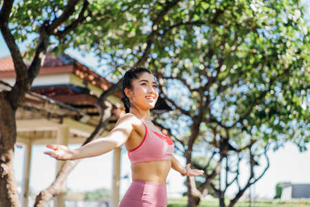 Attractive and fit young smiling Asian woman practicing yoga with stretched arms in outdoor park during morning routine for a healthy body