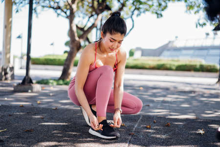Young sporty fit Asian woman tying shoelaces of running shoes while working out in outdoor park and taking break between training in the fresh air Banque d'images