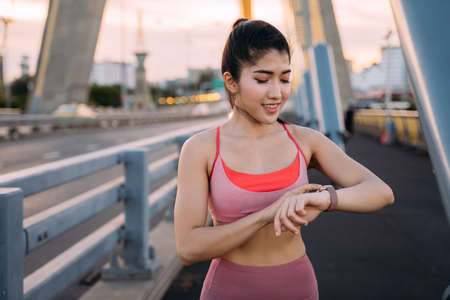 Young Asian female athlete checking smartwatch. Beautiful fitness woman running on bridge in morning for a fit and healthy lifestyle Banque d'images