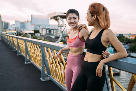 Two Asian smiling runners standing at bridge leaning against bridge edge. Young women relaxing and looking at sunrise and sunset while taking break from run Banque d'images