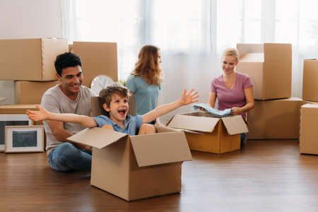 Playful little boy sitting in cardboard enjoying with young caucasian parents and sister unpacking stuff from carton boxes in new home Banque d'images