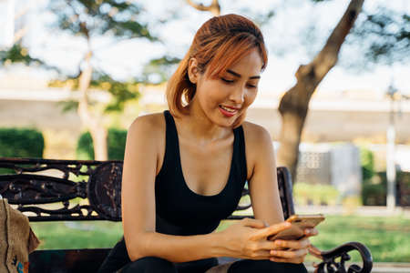 Young Asian fit woman in sportswear sitting on bench checking mobile phone. Asia girl taking a break during morning run in outdoor park