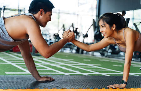Healthy smiling couple of man and woman giving high five to each other while pushing up in the fitness gym. Asian sporty people working out together. Teamwork and achievement concept Banque d'images