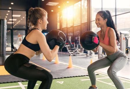 Happy young female athletic people performing squat exercises with friend and holding a medicine ball at fitness gym. Group of two confident women with healthy lifestyle working out together