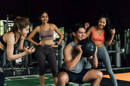 Group of people cheering on their Asian Chinese male friend doing squats with a medicine ball in fitness gym. Working out together as a teamwork. Encouragement and togetherness concept Banque d'images