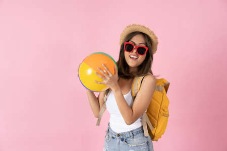 Young woman going on vacation holding inflatable ball and sunglasses against plain pink background Banque d'images
