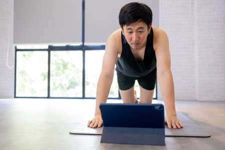 Young Asian man exercising at home while watching a video tutorial on tablet. Male fitness guy training indoors online