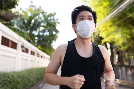 Young Asian man running with a face mask in the city. Male runner exercising and jogging on the street