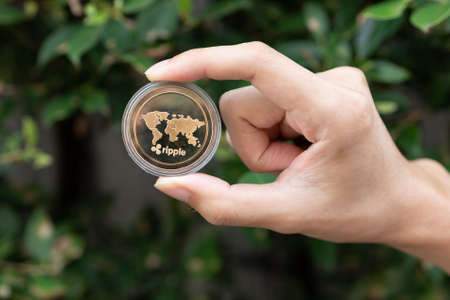 Young man holding XRP Ripple coin in hand with green bush in background - Cryptocurrency and Digital asset concept