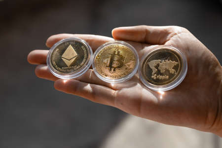 Young man holding Crypto tokens Bitcoin, Ethereum, Ripple on palm of hand - Cryptocurrency and Digital asset concept