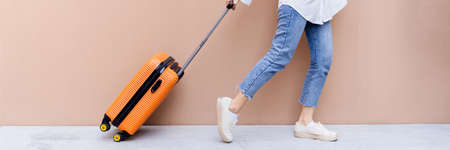 Young Asian girl happy while towing orange suitcase bumping in the air on concrete floor and desert sand colored wall background - Panorama banner Banque d'images