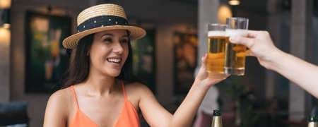 Beautiful and cheerful latin woman with hat sitting in outdoor pub restaurant clicking glass of beer for shots during lunch