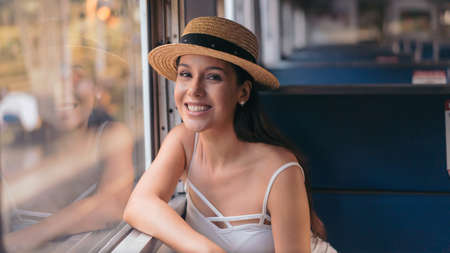 Portrait of beautiful young female tourist roaming around the city during vacation taking train as public transport while wearing a hat and smiling and looking at camera