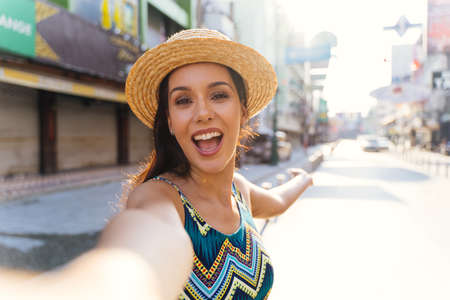 Young brunette woman using a mobile phone takes a selfie with attractive smile. Happy Hispanic girl traveler wear summer dress with hat waving to internet audience. Influencer and vlogging concept