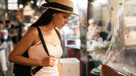 Young brunette woman traveler looks at street food stalls in china town market in Asia. 20s Hispanic girl tourist backpacking with summer hat on vacation trip. Foreigner in Asian city concept Banque d'images