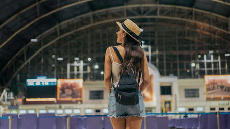 Rear view of young female traveller standing with backpack and hat at train station looking around for sign board to travel towards destination during vacation