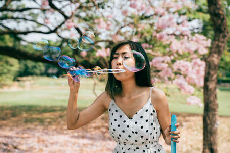 South East Asian ethnic 20s woman blowing air bubbles in the park Young Happy girl wears stylish dress with trees in background. Outdoor summer weekend activity - with copy space Banque d'images