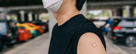 Young vaccinated man showing arms with adhesive plaster bandage after receiving Covid-19 vaccine injection with copy space. Coronavirus vaccination campaign in panorama banner Banque d'images
